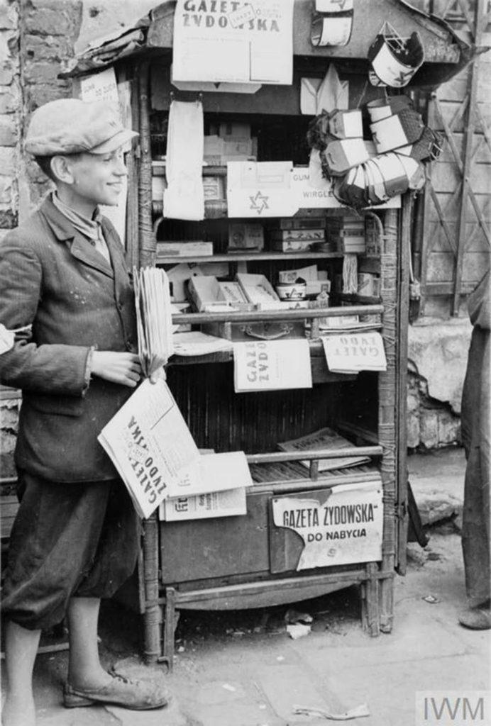 Молодой и веселый продавец газет и повязок, управляющий своим киоском на улице гетто (возможно, на Мурановской площади). Название газеты для продажи - «Газета Жидовская - Еврейская газета». Он также рекламирует жевательную резинку, Варшава, Польша, 1941 год.