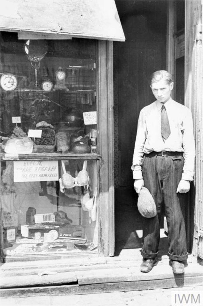 Молодой человек у входа в магазин. Обратите внимание, он снял шляпу, чтобы выполнить немецкий указ снимать головные уборы в присутствии немецкого персонала. Магазин предлагает свежие яйца, сладости и часы. Надпись на окне гласит: «Я покупаю старые часы по самым высоким ценам», Варшава, Польша, 1941 год.