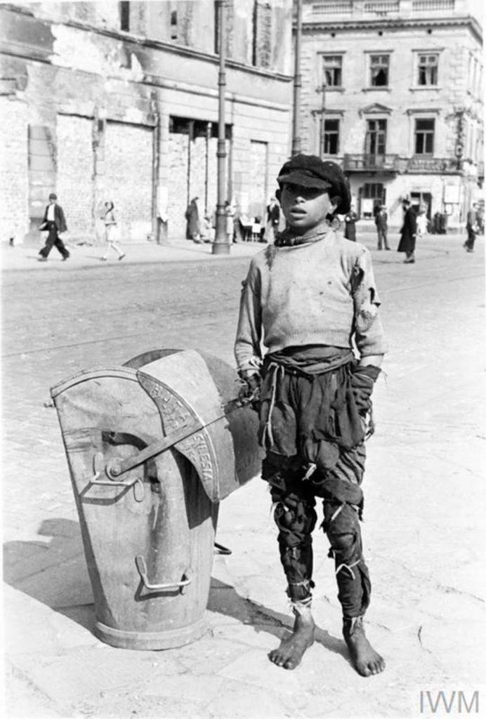 Подросток в рваной одежде стоит у контейнера для отходов (производства Силезского металлургического завода в Рыбнике), Варшава, Польша, 1941 год.