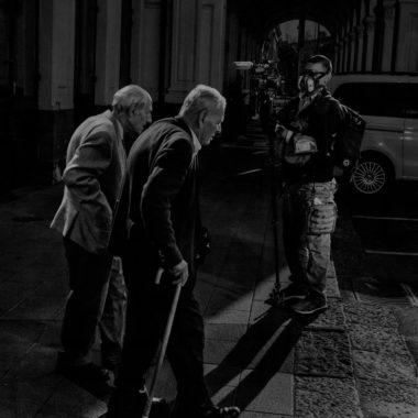 Два старика проходят мимо телеоператора в железнодорожном депо Катании. Накануне национального карантина последний поезд с пассажирами из Северной Италии опаздывает на три часа, Катания, остров Сицилия, Италия, 2020 год.