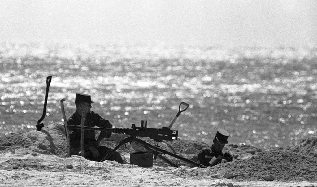 Два солдата сидят в песчаной землянке рядом с пулеметом на пляже в Ки-Уэсте, штат Флорида, 27 октября 1962 года.