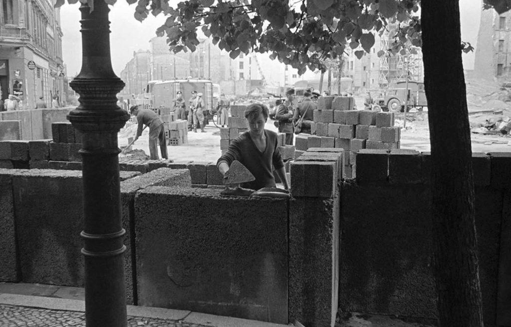 Молодой берлинец возводит бетонную стену, которая позже была увенчана колючей проволокой на границе сектора в разделенном городе 18 августа 1961 года.