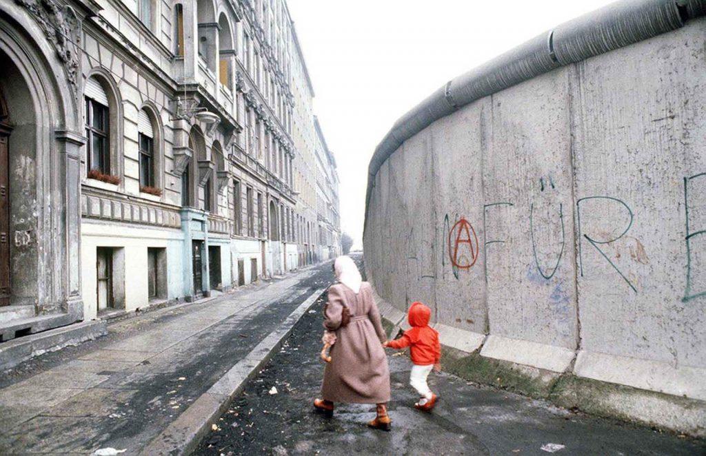 Женщина и ребенок проходят возле Берлинской стены.
