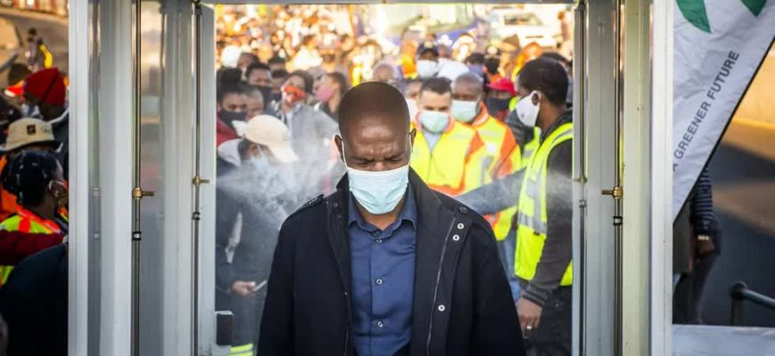 Житель Йоханнесбурга — самого крупного города ЮАР — проходит через санитарный коридор, 14 мая 2020 года