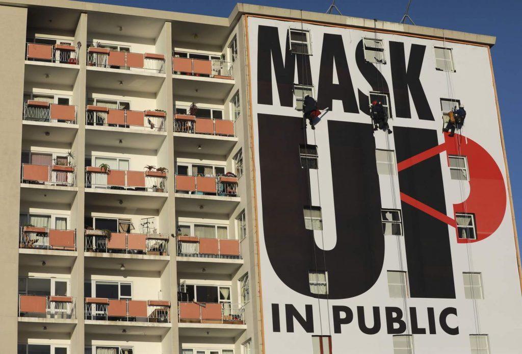 Плакат с призывом носить маски в общественных местах на стене жилого дома в Кейптауне, 16 мая 2020 года.