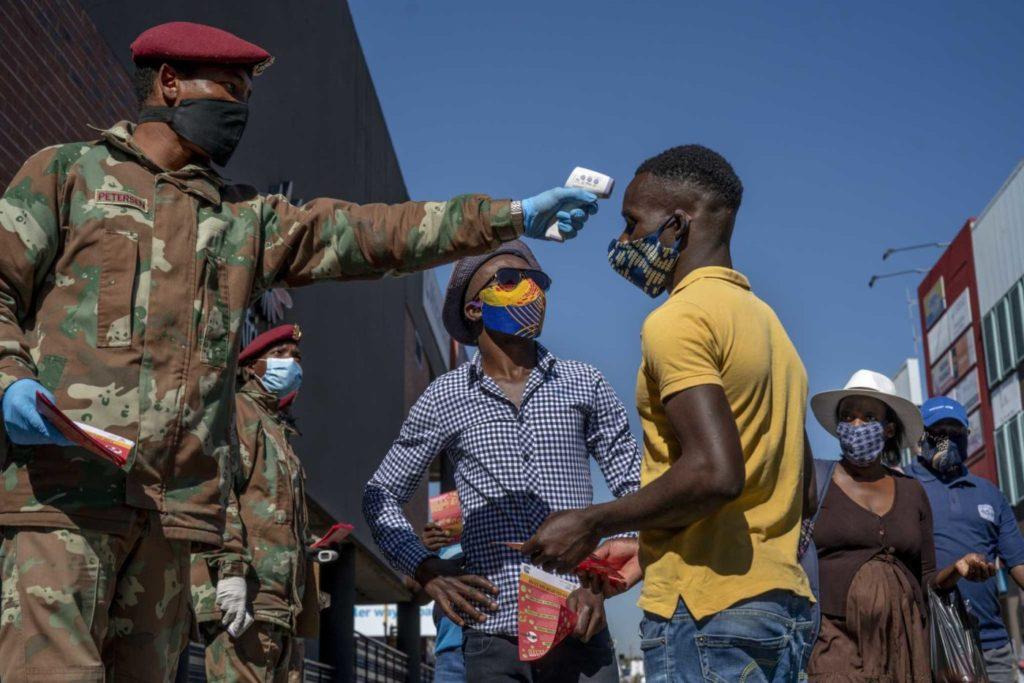 Военнослужащий проверяет температуру людей на стоянке маршрутных такси в Йоханнесбурге, 20 мая 2020 года.