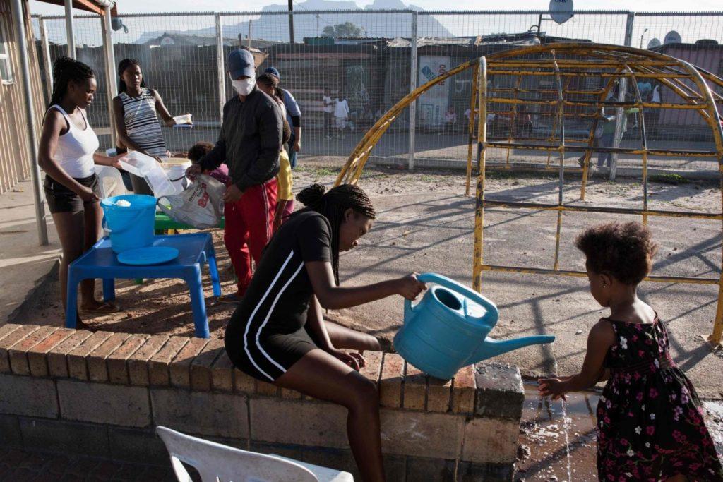 Девочка моет руки в детском саду в пригороде Кейптауна, 14 мая 2020 года.