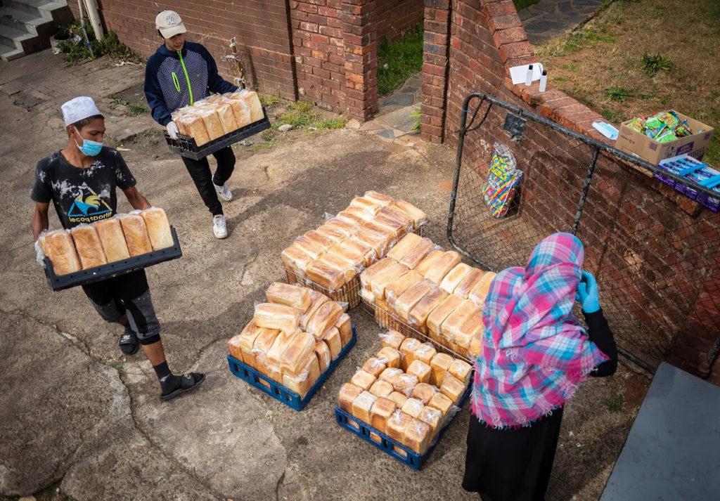 Сотрудники благотворительной организации из Йоханнесбурга готовят еду для раздачи во время карантина, 19 мая 2020 года. Covid-19, коронавирус в Африке.