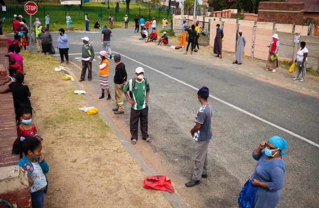 Жители Йоханнесбурга стоят в очереди за бесплатной едой во время карантина, 19 мая 2020 года. Covid-19, коронавирус в Африке.
