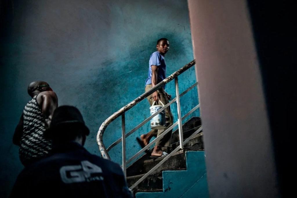 Мигрант, живущий в Йоханнесбурге, несет домой ведро воды, 14 мая 2020 года.