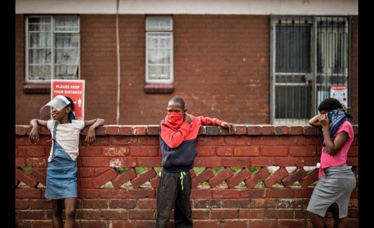 Дети держат дистанцию в очереди за бесплатной едой в Йоханнесбурге, 19 мая 2020 года.