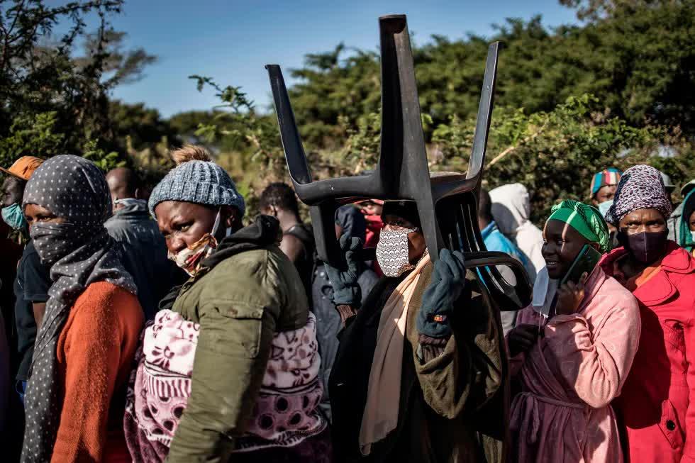 Женщина в очереди за масками и санитайзерами в пригороде Претории держит на голове стул, 20 мая 2020 года. Covid-19, коронавирус в Африке.