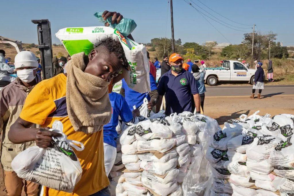 Жители Претории разбирают продукты, предоставленные благотворительными организациями, 20 мая 2020 года. Covid-19, коронавирус в Африке.