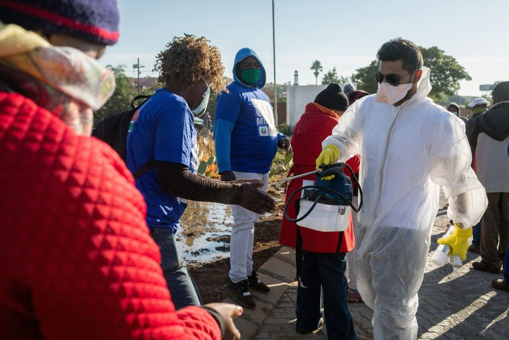 Волонтер в Претории дезинфицирует людям руки перед получением бесплатных продуктов, 20 мая 2020 года.