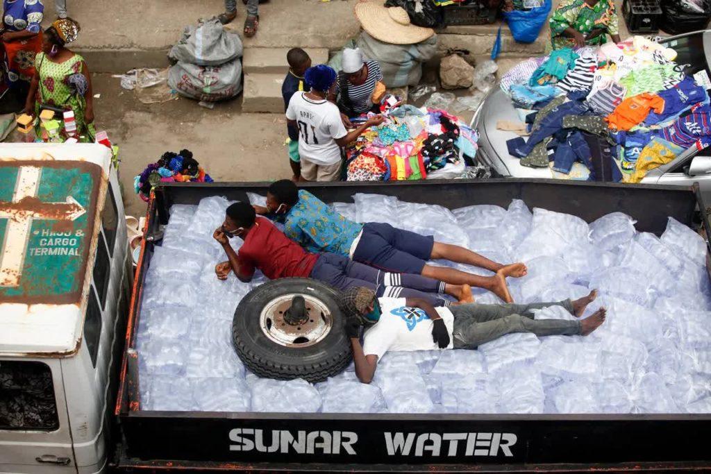 Мужчины лежат на пакетах с водой, предназначенных для продажи на рынке нигерийского города Лагос, 20 мая 2020 года.