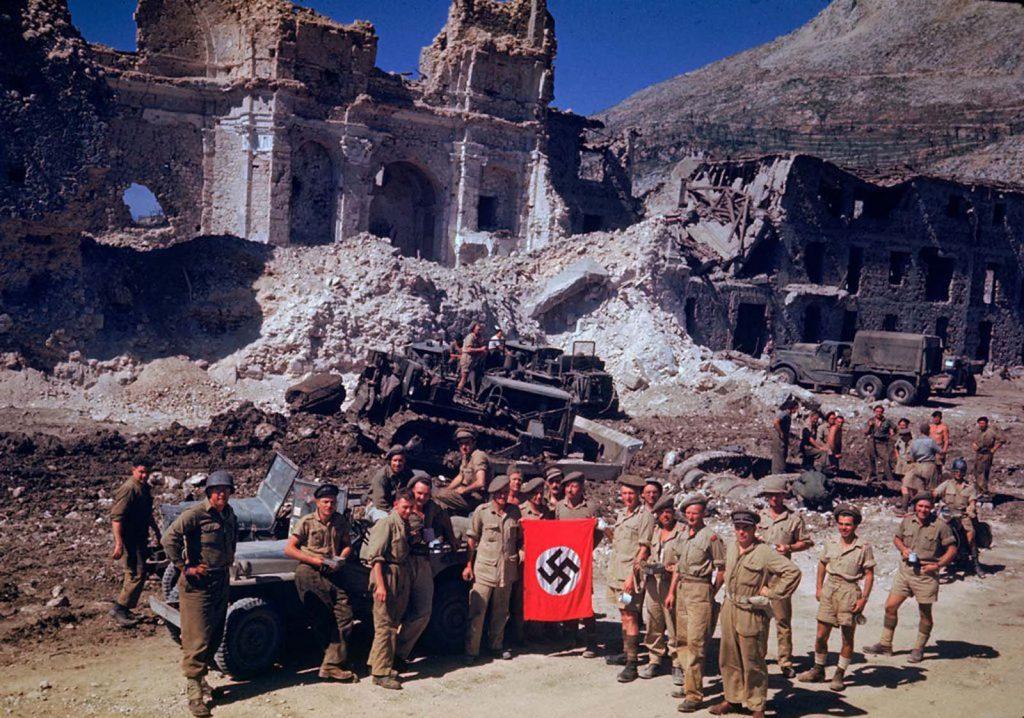 Британские и Южноафриканские солдаты с нацистским трофейным флагом, на заднем плане боевые инженеры на бульдозерах расчищают путь через обломки разбомбленного города, Вторая мировая война.