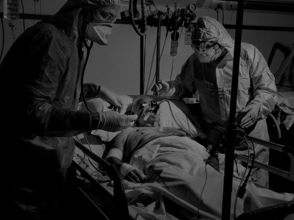"""Мужчина с коронавирусом (COVID-19) подключенный к аппарату вентиляции легких, отделении интенсивной терапии больницы """"Канниццаро"""" в Катании, остров Сицилия, Италия, 2020 год."""