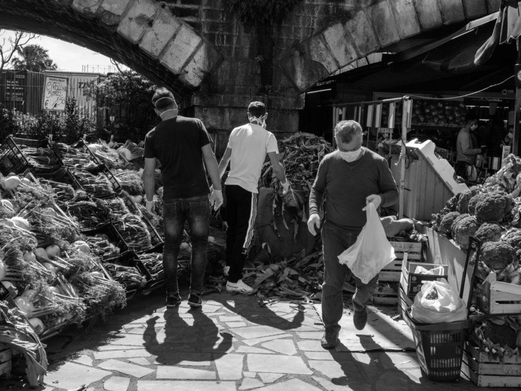 Покупатели, прибывшие из сельской местности, покупают артишоки и апельсины. Это последний день, когда продавцам разрешается распространять продукцию на рынках, Катания, остров Сицилия, Италия, 2020 год.