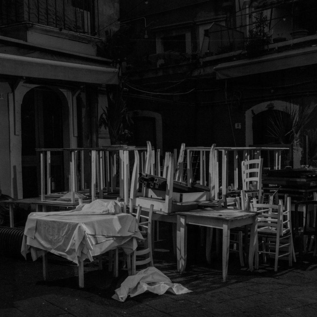 На небольшой общественной площади в Катании нагромождены столы и стулья. Хозяева, по-видимому, в спешке покидали свой ресторан, Катания, остров Сицилия, Италия, 2020 год.