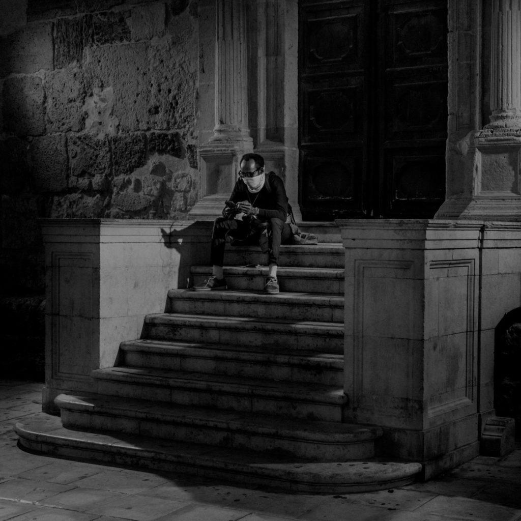 Одинокий мужчина с телефоном на ступеньках церкви в Сиракузах, остров Сицилия, Италия, 2020 год.