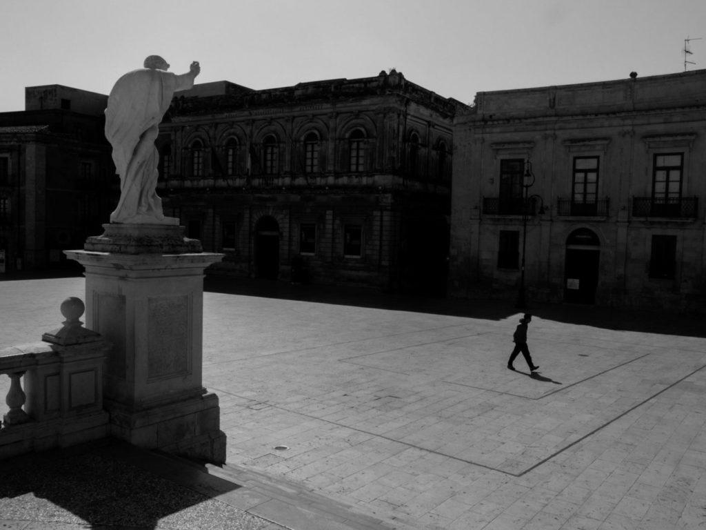 Площадь Санта-Лючия в Сиракузах обычно кишит людьми. «Я ждал час, и не увидел ни души», – вспоминает Маджоли. «Потом эта одинокая фигура прошла мимо», остров Сицилия, Италия, 2020 год.