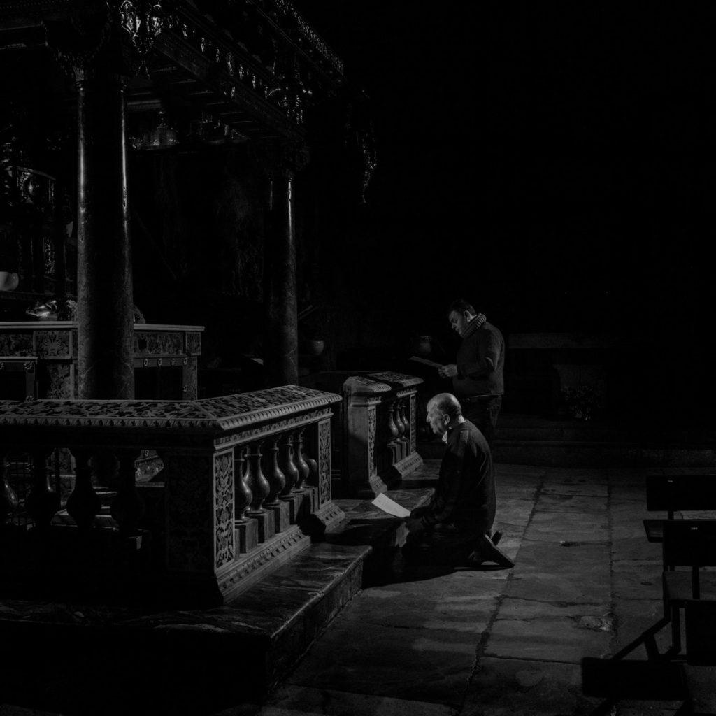 """В Палермской церкви Санта-Розалия священник c помощником молятся в пустом святилище, читая """"Молитву в это трудное время"""", написанную архиепископом Палермо, остров Сицилия, Италия, 2020 год."""
