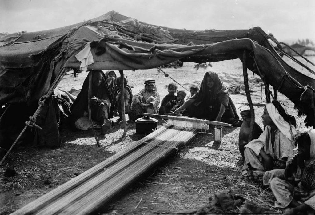 Женщина - бедуин плетет ткань, а ее семья смотрит, 1898 год.