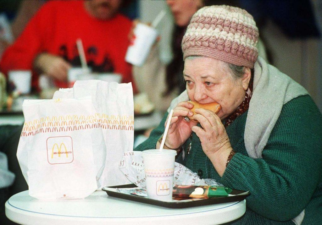 Пожилая женщина ест свой гамбургер.