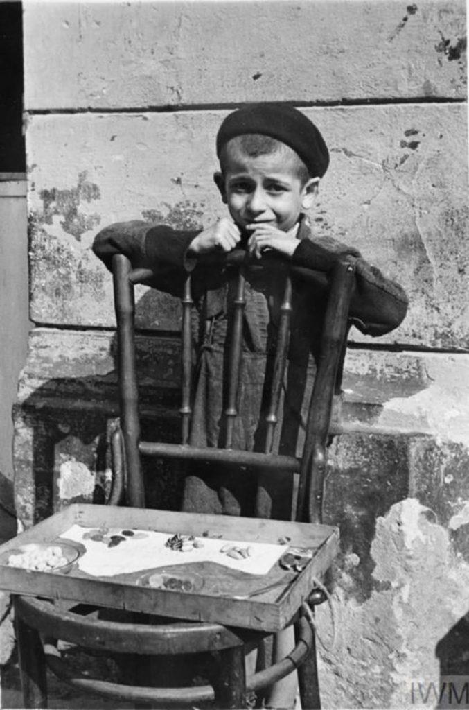 Мальчик продает сладости, выложив их на сломанный стул, Варшава, Польша, 1941 год.