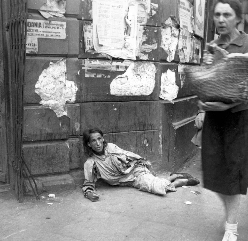 Обессиленная от голода женщина, лежит на асфальте, Варшавское Гетто, Польша, 1941 год.