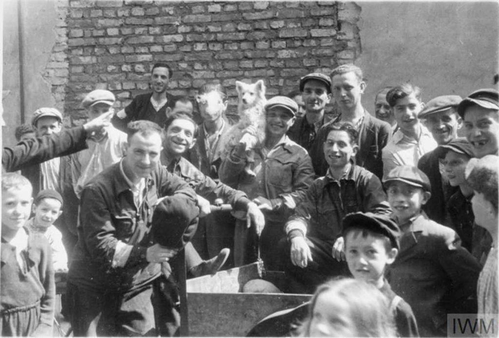 Группа еврейских мужчин и детей позирует фотографу на улице, Варшавское гетто. Обратите внимание на человека посередине, держащего собаку на плече, Варшава, Польша, 1941 год.