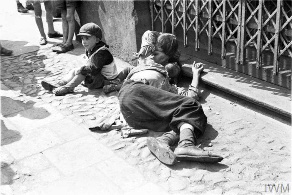 Голодный мужчина (отец?) И двое истощенных детей, просящих милостыню на улице, Варшава, Польша, 1941 год.