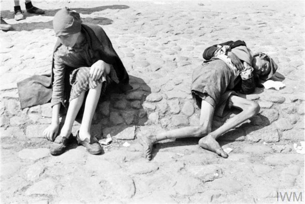 Двое истощенных детей, один из которых спит или без сознания, просят милостыню на улице, Варшава, Польша, 1941 год.