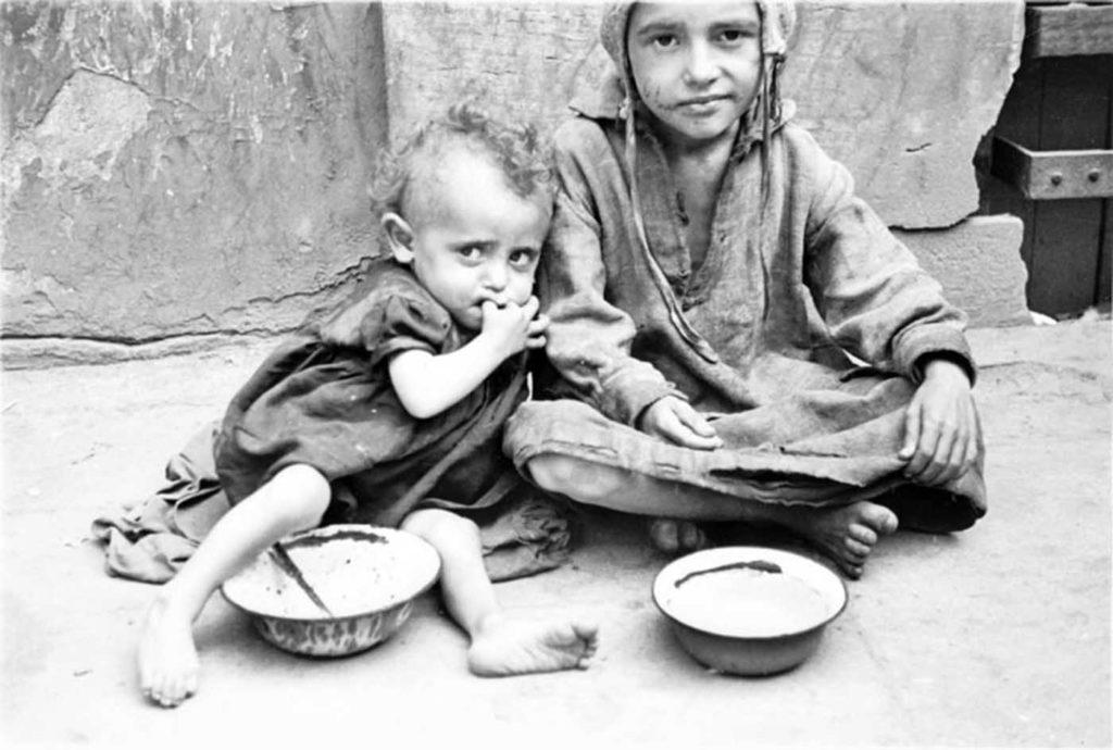 Двое маленьких детей просят еду на улице, Варшава, Польша, 1941 год.