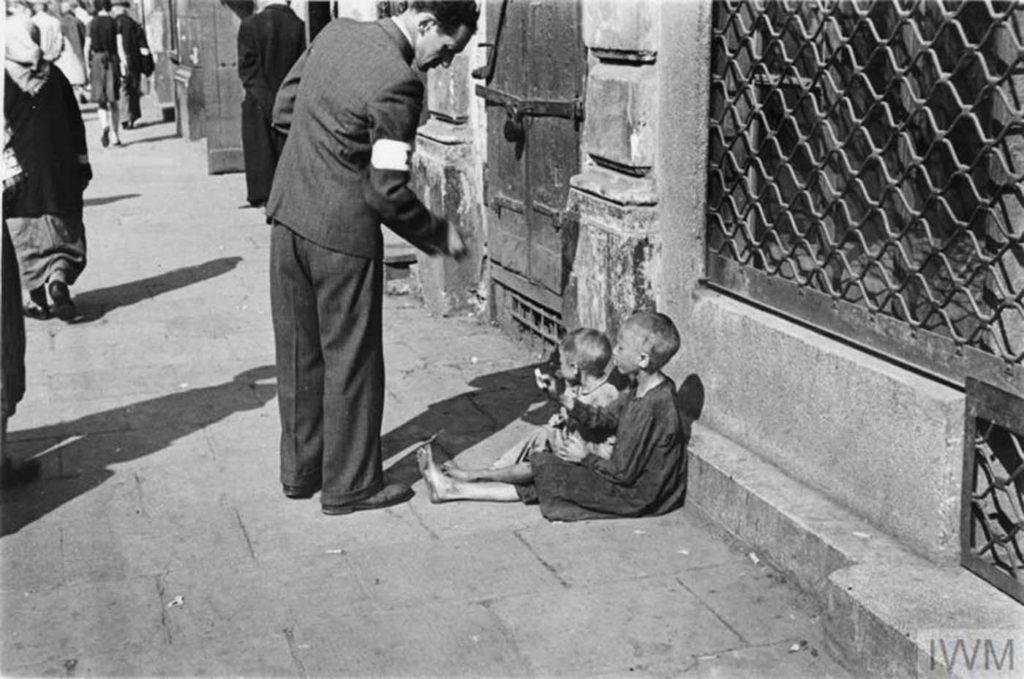 Прохожий дает деньги двум детям, Варшава, Польша, 1941 год.