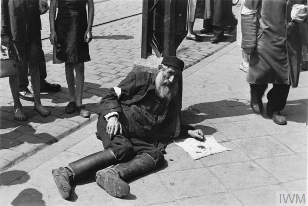 Пожилой мужчина лежит на асфальте, Варшава, Польша, 1941 год.