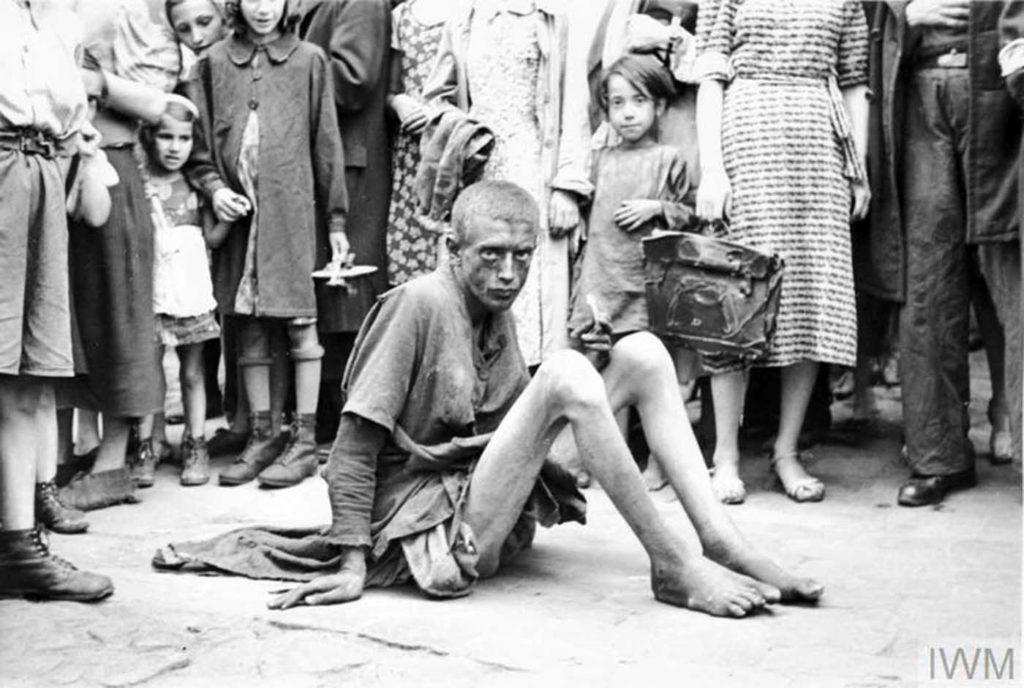 Истощенный мальчик сидит на асфальте. Обратите внимание на толпу пешеходов вокруг него, в том числе детей с игрушками, Варшава, Польша, 1941 год.