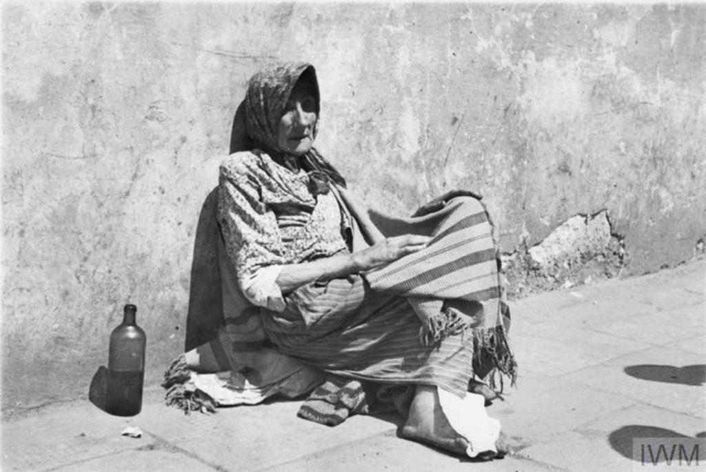 Пожилая женщина, попрошайничает на улице, Варшава, Польша, 1941 год.