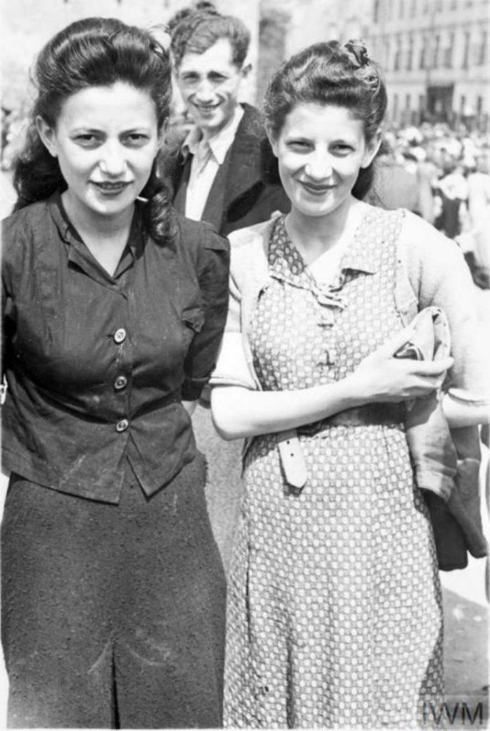 Две хорошо одетые женщины, скорее всего, сестры, позируют фотографу на уличном рынке, Варшава, Польша, 1941 год.