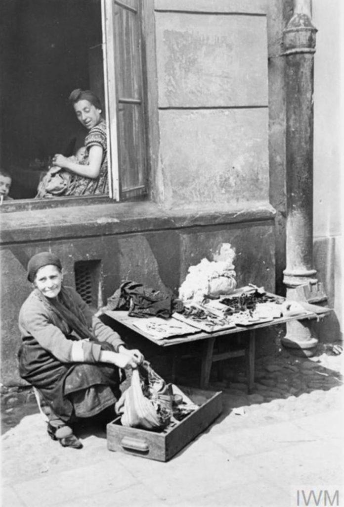 Пожилая женщина продает свои последние вещи на улице, Варшава, Польша, 1941 год.