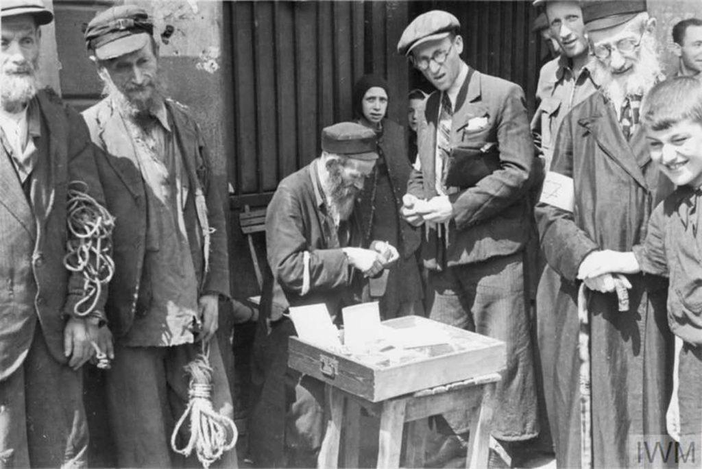 Мужчина продает вещи, слева стоят два пожилых мужчины, которые пытаются продать веревки, Варшава, 1941 год.