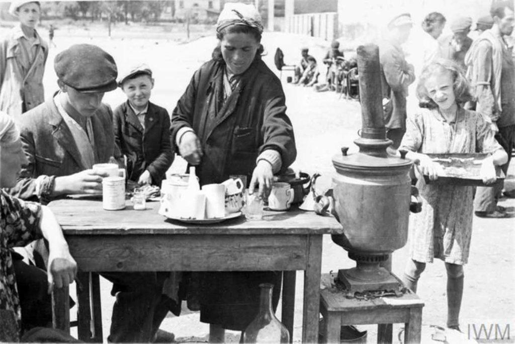 Женщина продает чай на улицах гетто, аналог летнего кафе, Варшава Гетто, Польша, 1941 год.