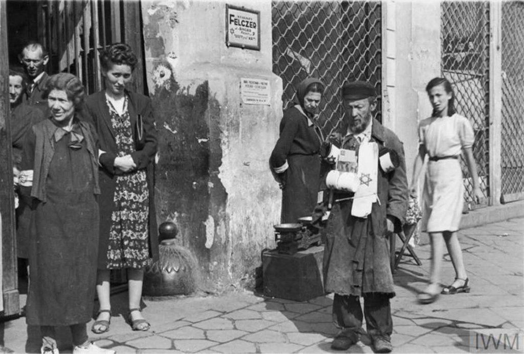 Уличный продавец нарукавных повязок и группа пешеходов на улице Заменхофа, 18 (вероятно), Варшава, Польша, 1941 год.