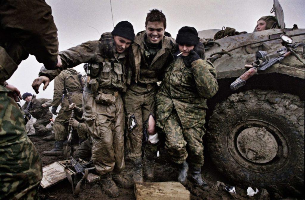 Российские морские пехотинцы помогают раненному товарищу, который попал в засаду возле села Центарой, декабрь 1999 года. Вторая Чеченская война.