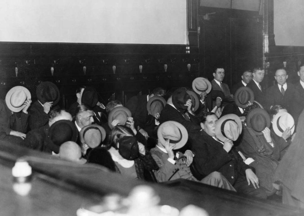 Зрители на суде над Аль Капоне так боялись возмездия, что закрывали свои лица. 1931 год. Чикаго, Иллинойс. Источник: Ullstein Bild / Getty Images