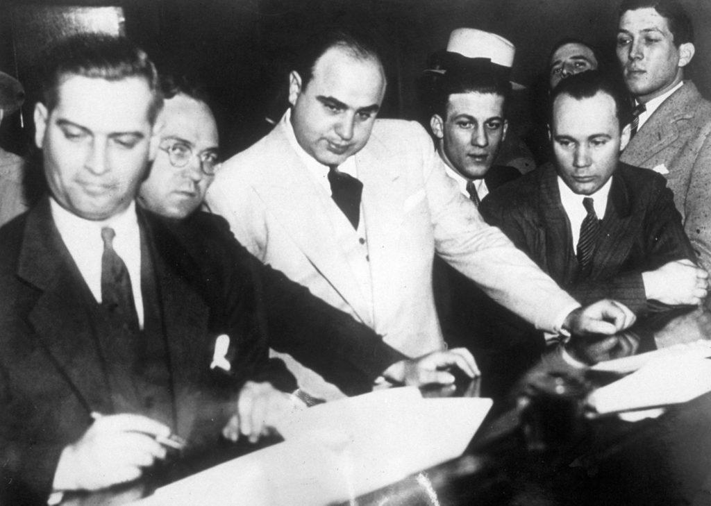 Аль Капоне подписывает залог на 50 000 долларов в федеральном здании суда после того, как его обвинили в уклонении от уплаты налогов. Источник: Topical Press Agency/Getty Images