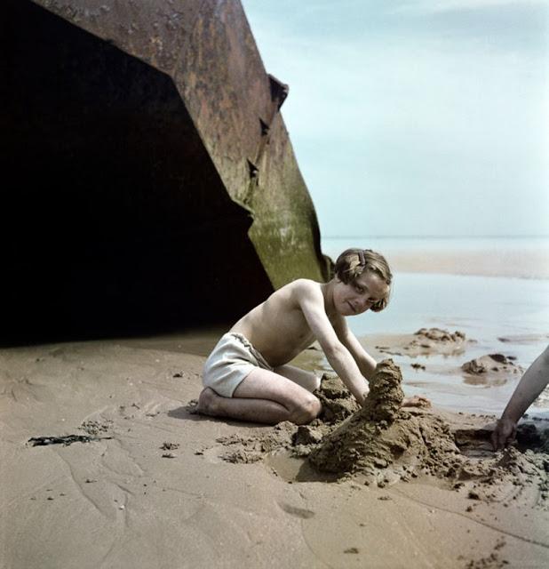 Ребенок строит замок из песка возле обломков на пляже, Нормандия, 1947 год. David Seymour/Magnum Photos Цветные фотографии Нормандии после Второй мировой Войны