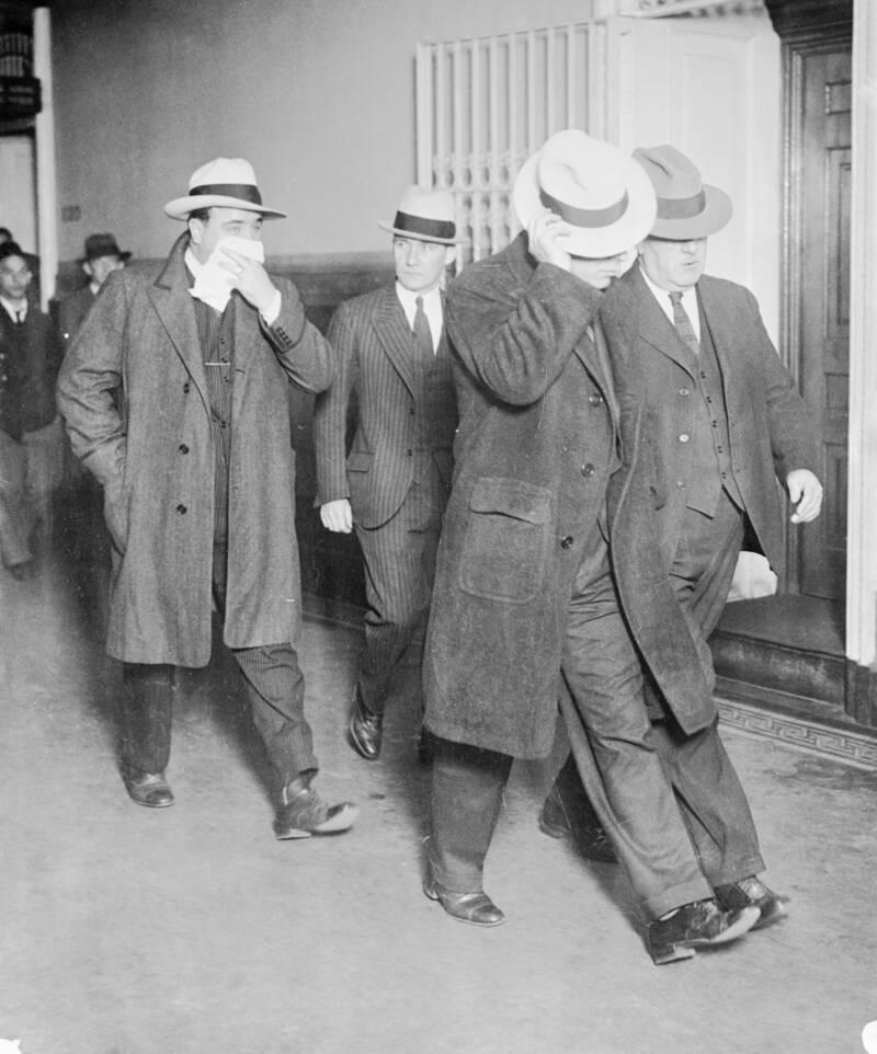 Капоне и его телохранитель Фрэнк Клайн прикрывают лица, идя в сопровождении полицейских детективов. Источник: Bettmann / Getty Images