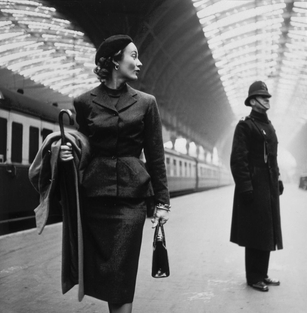 Фотомодель Лиза Фонсагривс позирует с английским полицейским на заднем, железнодорожная станция, фото для журнала Harper's Bazaar, 1951 году. Фотограф Тони Фрисселл