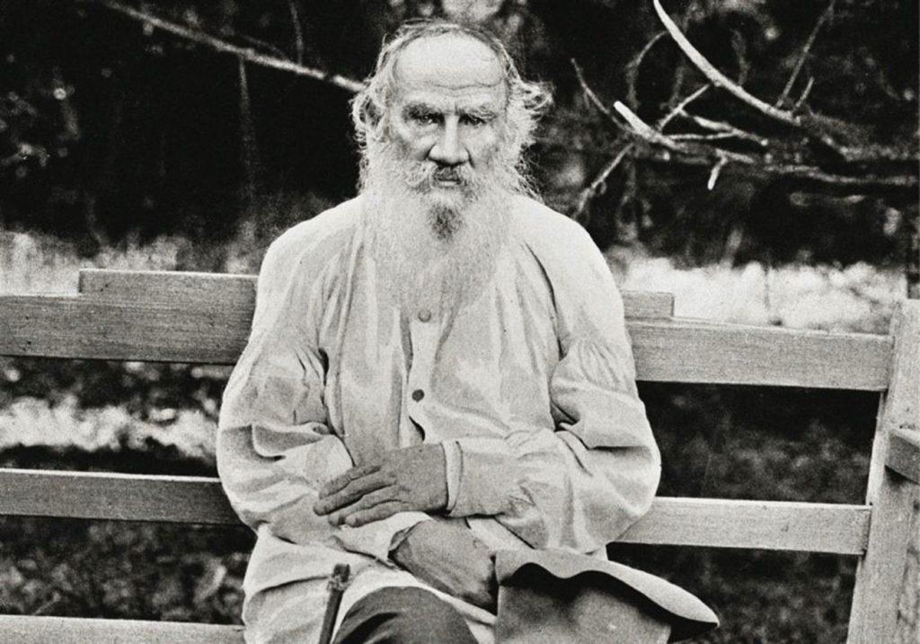 Лев Толстой сидит на скамейке.